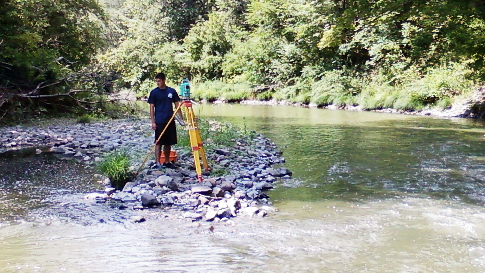 Young surveyor with equipment at a creek in Columbia County