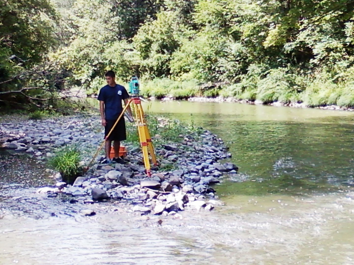 Young surveyor with equipment at creek.